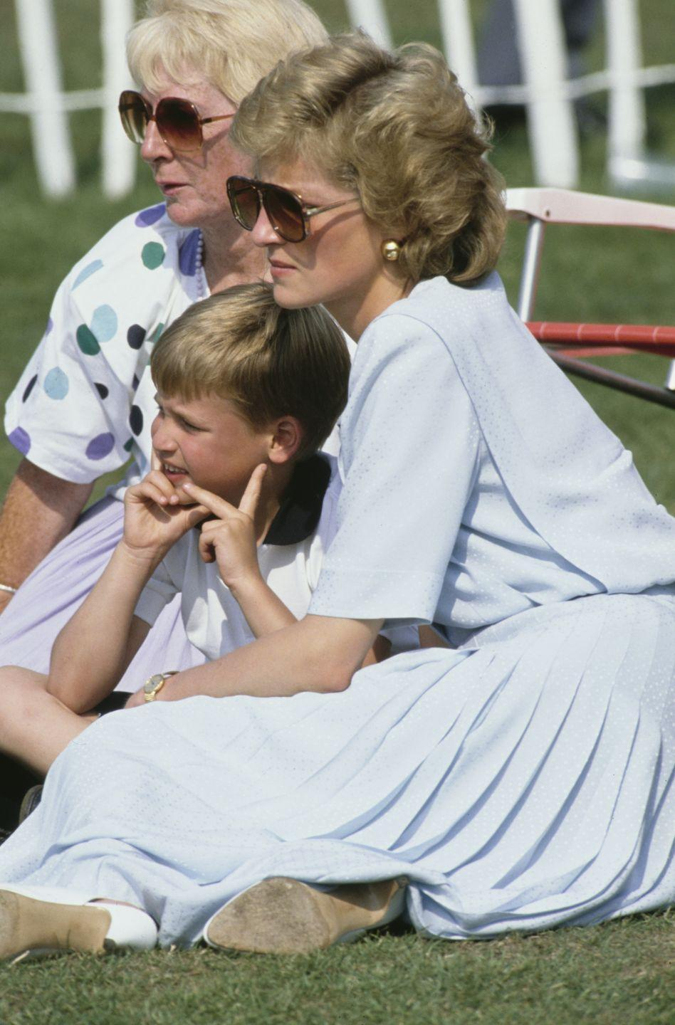 <p>Sitting with her mother, Frances Shand Kydd, and her eldest son Prince William at a Cartier International Polo match in Windsor.</p>