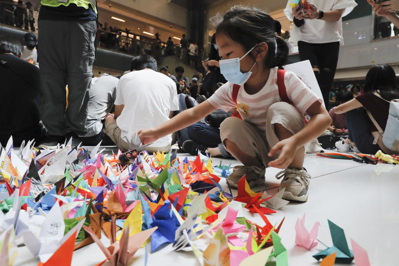 "A child arranges origami cranes used in an anti-government rally inside a shopping mall at the Sha Tin district in Hong Kong, Sunday, Sept. 22, 2019. Young protesters, many wearing masks to disguise their identity, filled the open area of a Hong Kong shopping mall Sunday and folded paper ""origami"" cranes in the latest twist in a pro-democracy movement that has stretched into a fourth month. (AP Photo/Kin Cheung)"