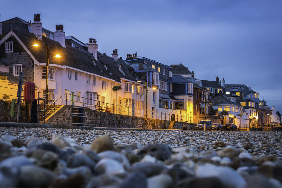 Seafront cottages warmly illuminated against the blue dusk sky overlooking the pebble beach at Lyme Regis, in Dorset, UK.