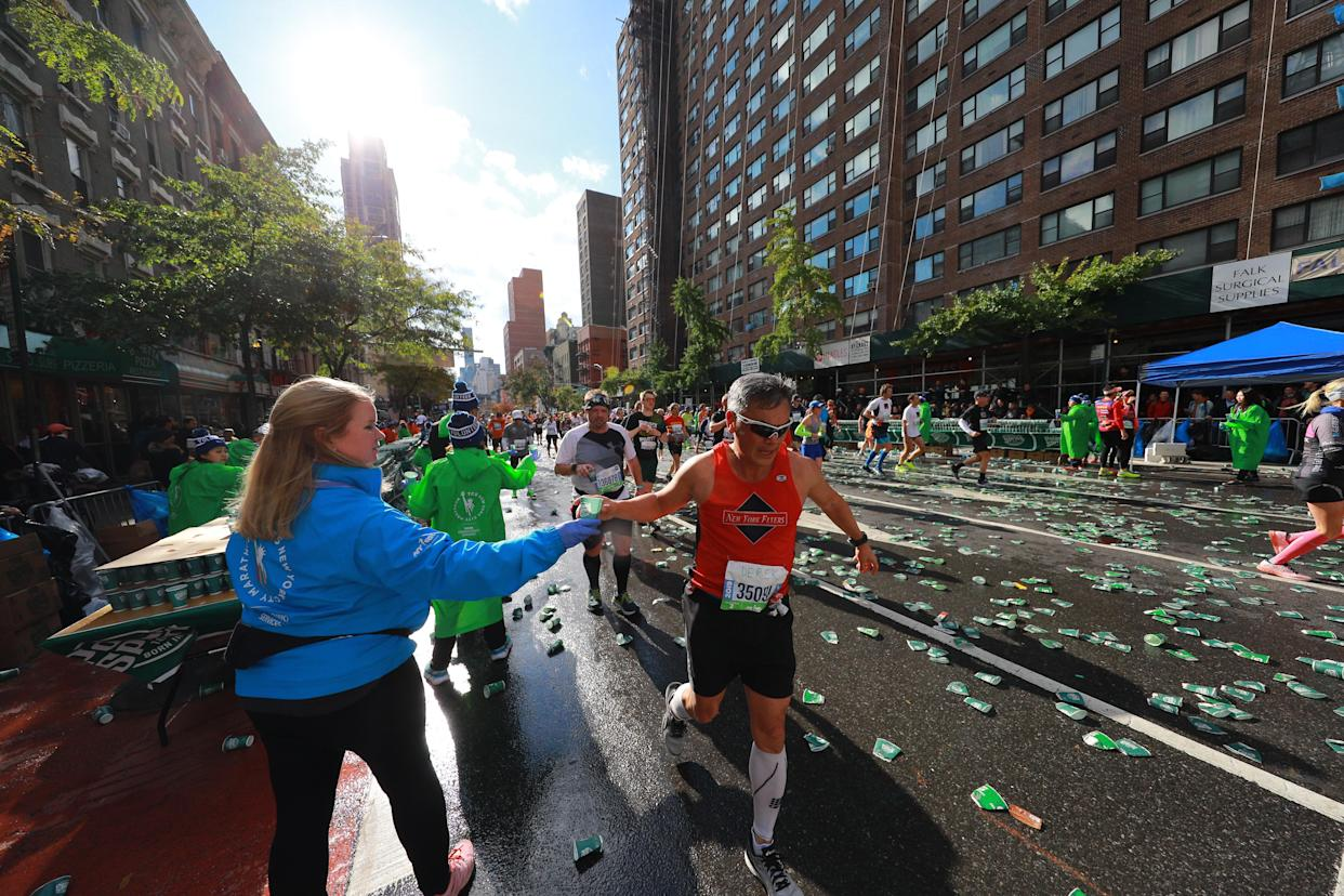 Runners are handed cups of water by volunteers on First Avenue during the New York City Marathon. (Photo: Gordon Donovan/Yahoo News)