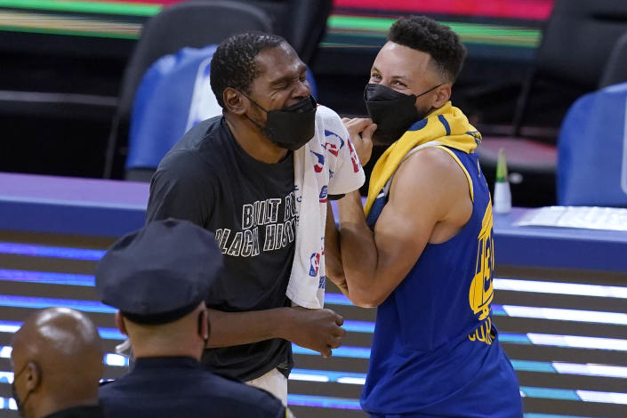Kevin Durant and Stephen Curry wear masks while laughing.