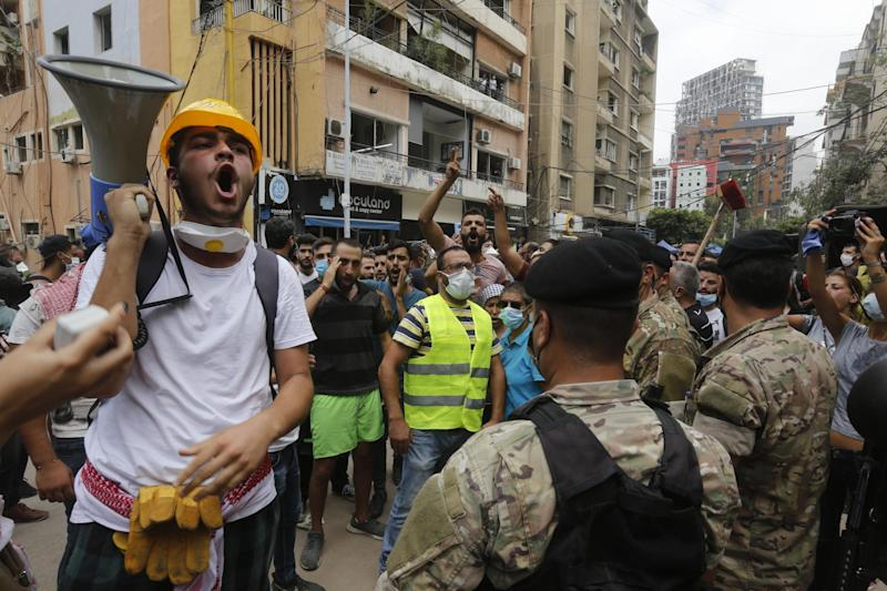 Members of the army hold back demonstrators, angry with the government negligence that allegedly contributed to Tuesday's explosion: Marwan Tahtah/Getty