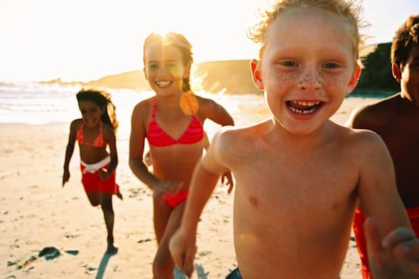 portrait of a group of children running on the beach