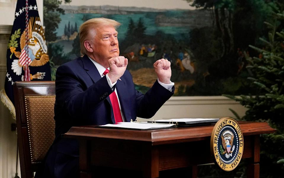 President Donald Trump gestures as he participates in a video teleconference call with members of the military on Thanksgiving - AP