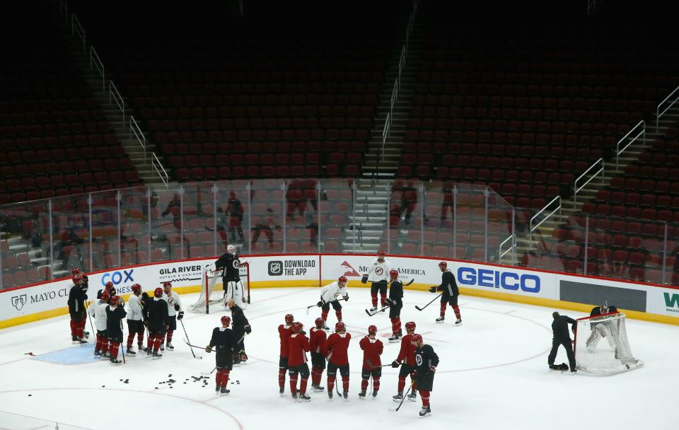 The Arizona Coyotes players and coaches pause on the ice during NHL hockey practice at Gila River Arena Monday, July 13, 2020, in Glendale, Ariz. (AP Photo/Ross D. Franklin)