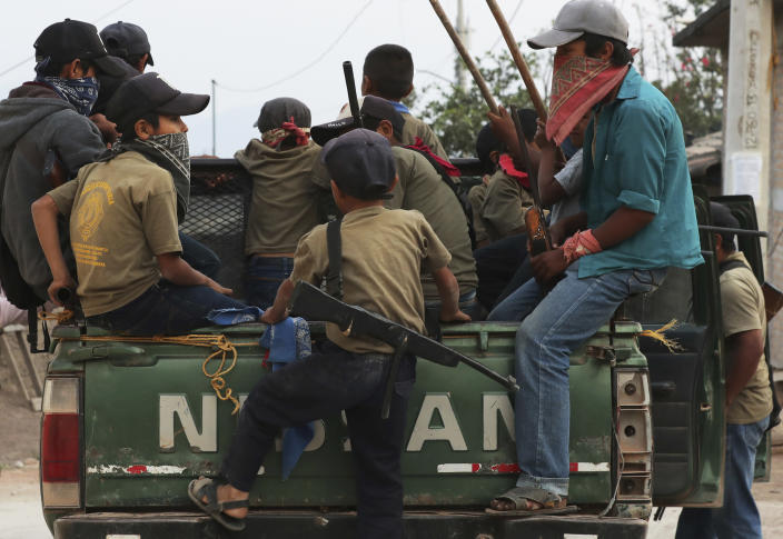 Children, some carrying real weapons and others with fake ones, patrol their community aboard a pick-up truck as part of a display by community leaders to call the government's attention to their town's plight in Ayahualtempa, Guerrero state, Mexico, Wednesday, April 28, 2021. Community police say they don't worry their children will be used by criminals because they teach them guns are to defend their communities. (AP Photo/Marco Ugarte)