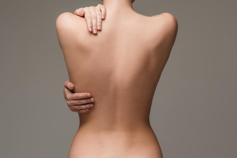 woman's body on gray background. The nude woman back