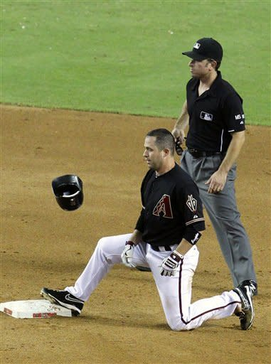 Arizona Diamondbacks' John McDonald, left, watches his helmet bounce after he threw it down after being tagged out at second base on an inning-ending double play during the fifth inning of a baseball game against the San Diego Padres, Saturday, Aug. 25, 2012, in Phoenix. Umpire Chris Guccione looks on. (AP Photo/Ross D. Franklin)