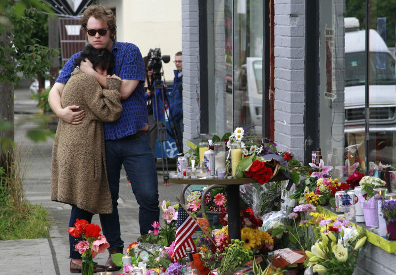 Jonny and Ali, who both declined to give their last names, comfort each other at the scene of where a gunman killed four people and severely wounded another in a cafe a day earlier, Thursday, May 31, 2012, in Seattle. The pair were close friends of two of the men killed there. Police say the assailant later killed a woman during a carjacking before shooting himself. As officers closed in during a widespread manhunt on Wednesday, the suspect put a gun to his head and pulled the trigger and later died at a hospital. (AP Photo/Elaine Thompson)