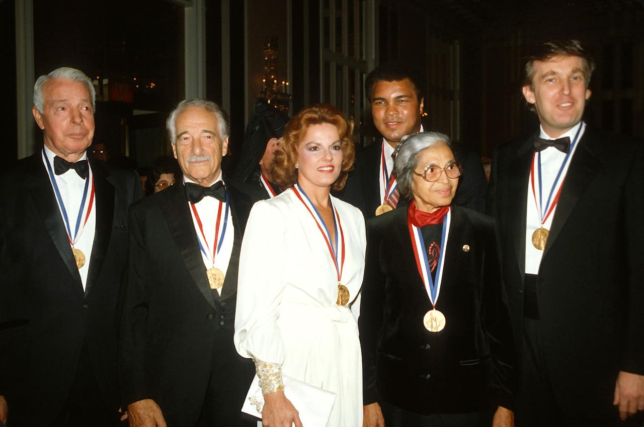 <p>From left: Joe DiMaggio, Victor Borge, Anita Bryant, Muhammad Ali, Rosa Parks and Donald Trump pose for a photograph after receiving the Ellis Island Medal of Honor on Oct. 27, 1986, in New York City. <i>(Photo: Yvonne Hemsey/Getty Images)</i> </p>