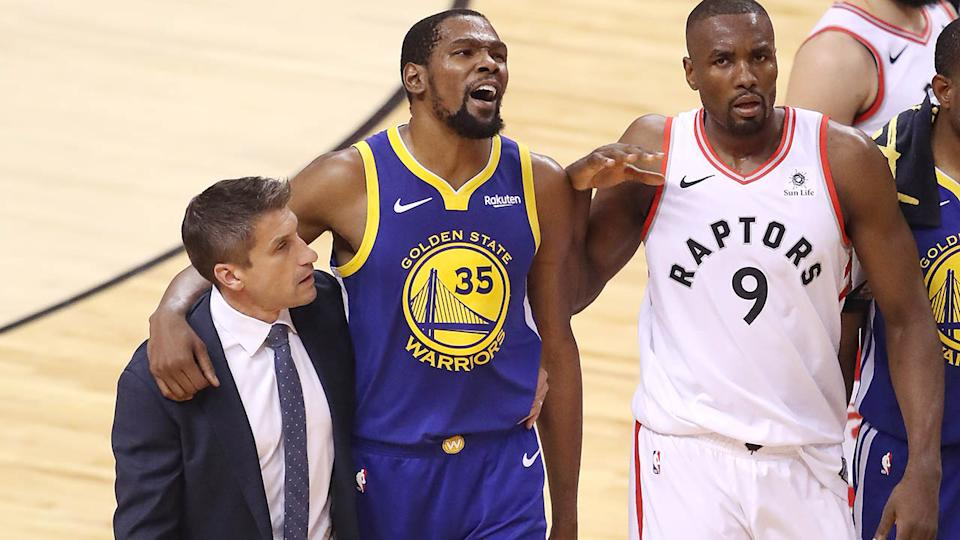 Kevin Durant is assisted off the court. (Photo by Claus Andersen/Getty Images)