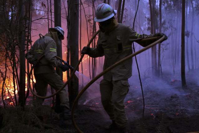 <p>Portuguese National Republican Guard firefighters work to stop a forest fire from reaching the village of Avelar, central Portugal, at sunrise Sunday, June 18 2017. (Armando Franca/AP), </p>