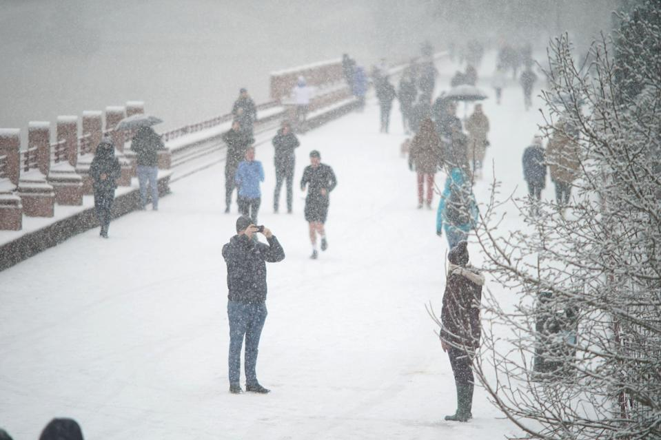 <p>People walking in the snow in Battersea Park on Sunday</p> (PA)