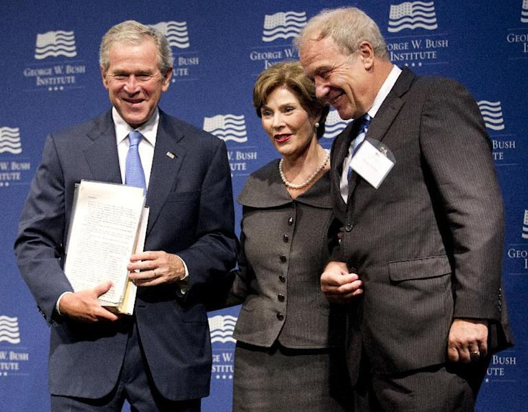 Former President George W. Bush, with former first lady Laura Bush, center, is presented with a collection of writings by former Czech President Vaclav Havel by Martin Palous, head of the Vaclav Havel Library Foundation during a gathering to celebrate the successes of dissidents and activists in their fight to be free, Tuesday, May 15, 2012, at the George W. Bush Presidential Center in Washington. (AP Photo/Manuel Balce Ceneta)