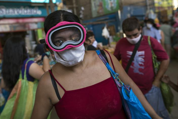 A woman wears a scuba and surgical mask amid the spread of the new coronavirus while shopping at a market in Lima, Peru, Monday, March 23, 2020. (AP Photo/Rodrigo Abd)