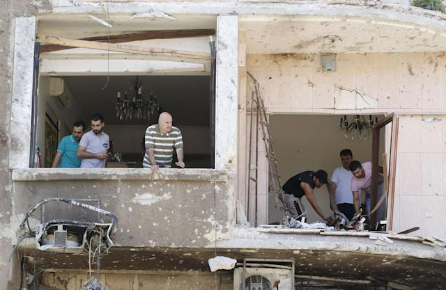 <p>Syrian men inspect the damage inside a building at the site of a suicide bomb attack in the capital Damascus' eastern Tahrir Square district, on July 2, 2017. (Louai Beshara/AFP/Getty Images) </p>