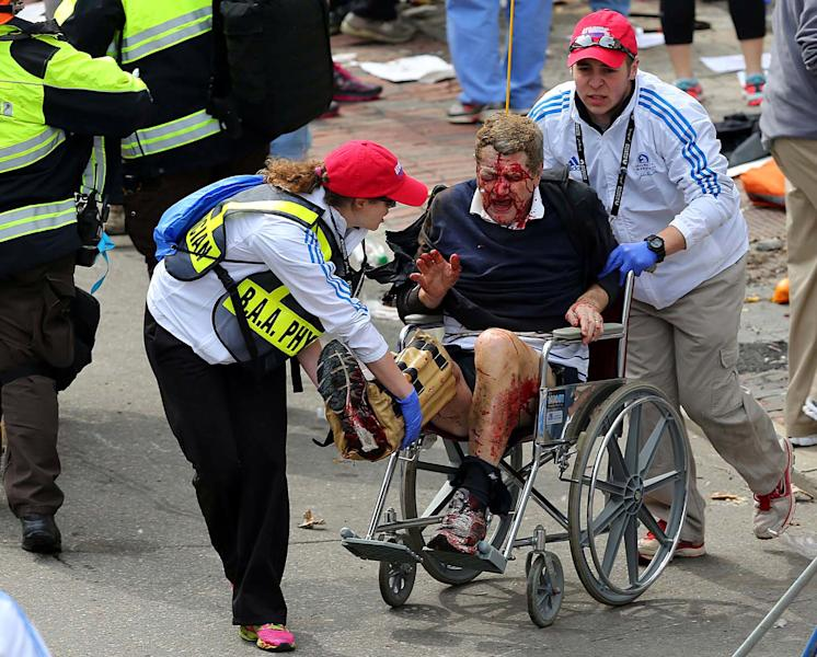 Medical workers aid an injured man at the 2013 Boston Marathon following an explosion in Boston, Monday, April 15, 2013. Two bombs exploded near the finish of the Boston Marathon on Monday, killing at least two people, injuring at least 22 others and sending authorities rushing to aid wounded spectators. (AP Photo/The Boston Globe, David L. Ryan) MANDATORY CREDIT