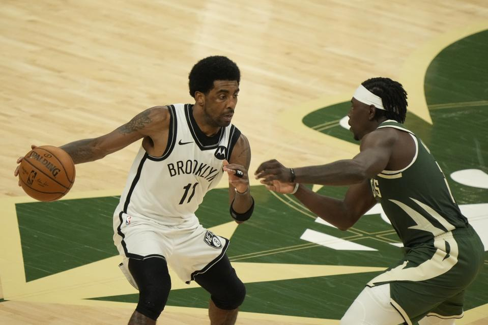 Brooklyn Nets' Kyrie Irving tries to drive past Milwaukee Bucks' Jrue Holiday during the second half of Game 3 of the NBA Eastern Conference basketball semifinals game Thursday, June 10, 2021, in Milwaukee. (AP Photo/Morry Gash)