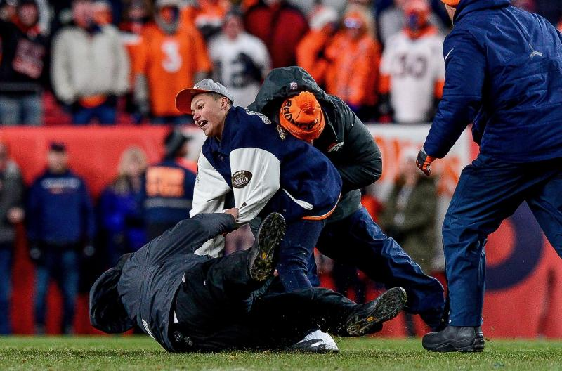 A security guard suffered a serious ankle injury after a fan ran onto the field in Denver. (Dustin Bradford/Getty Images)