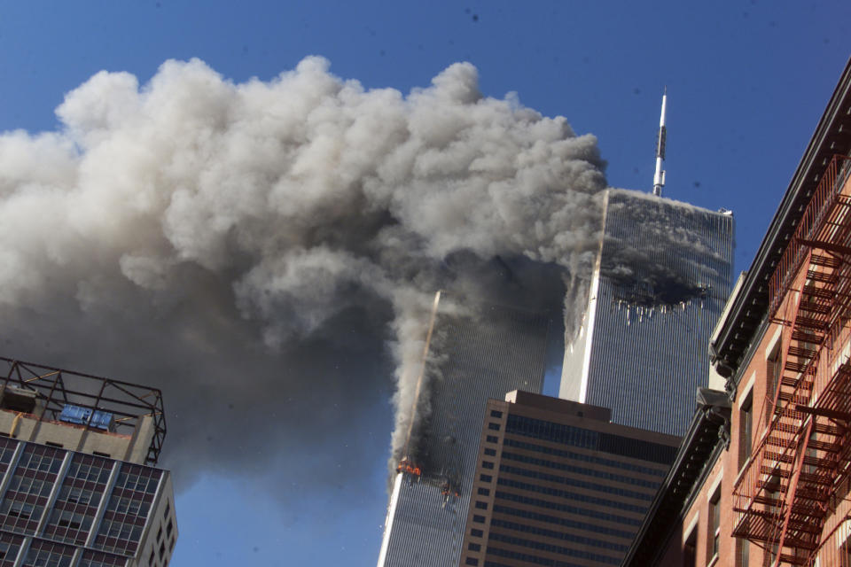 FILE - In this Sept. 11, 2001 file photo smoke rises from the burning twin towers of the World Trade Center after hijacked planes crashed into the towers, in New York City. On Friday, Feb. 15, 2019, Rupa Bhattacharyya, the September 11th Victim Compensation Fund special master, announced that the compensation fund for victims of the Sept. 11, 2001 terror attacks will cut future payments by 50 to 70 percent because the fund is running out of money. (AP Photo/Richard Drew, File)