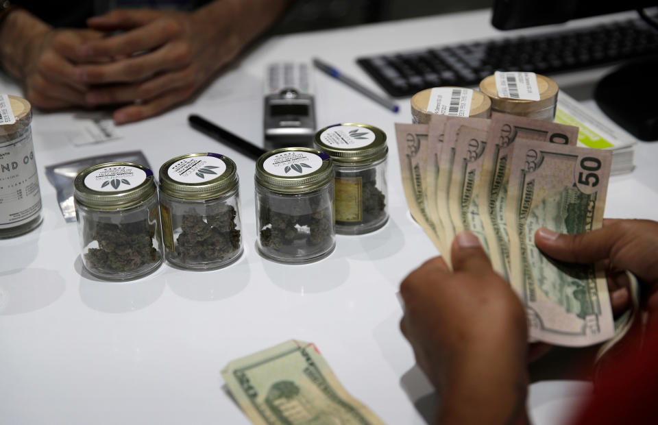 FILE – In this July 1, 2017 file photo, a person buys marijuana at the Essence cannabis dispensary in Las Vegas. . (AP Photo/John Locher, File)