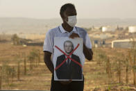 An Israeli Arab protester wears a face masks to help prevent the cooranvirus while holding a defaced picture of French President Emmanuel Macron, during a small demonstration protesting published caricatures of the Prophet Muhammad they deem insulting and blasphemous, in Hura, a Bedouin village in the Negev desert, Israel, Monday, Oct. 26, 2020. (AP Photo/Sebastian Scheiner)