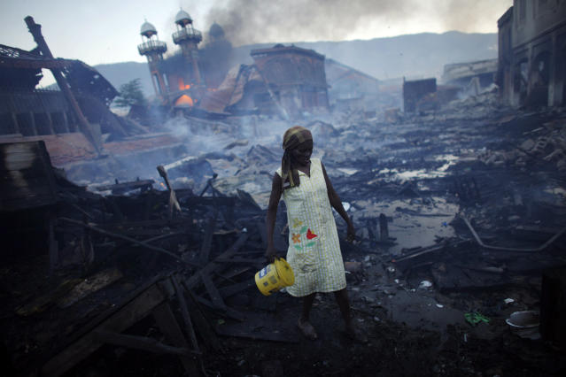 <p>A woman walks near a fire at the Hyppolite iron market in downtown Port-au-Prince, Haiti, Jan. 29, 2010. (Photo: Jorge Silva/Reuters) </p>