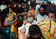 FILE PHOTO: People wearing protective masks exit a railway station amid the spread of the coronavirus disease (COVID-19) in Mumbai