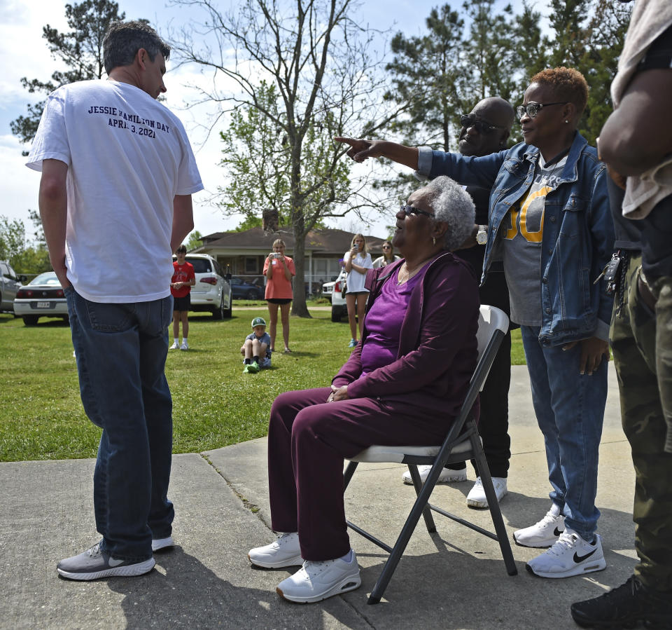 "Andrew Fusaiotti, left, turns around to show Jessie Hamilton, seated, the back of his shirt as Hamilton's daughter, Yonetta Tircuit, right, points as LSU FIJI graduates gather to surprise their former house kitchen staff member, Saturday, April 3, 2021, to pay off her mortgage and celebrate ""Jessie Hamilton Day"" in Baker, La. (Hilary Scheinuk/The Advocate via AP)"