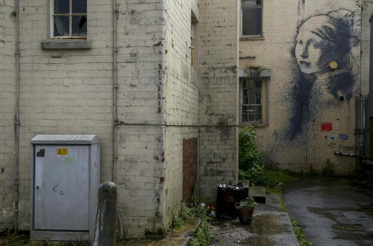 """Like many other spots the mysterious artist has decorated in his purported home city of Bristol, the courtyard beneath his """"The Girl with a Pierced Eardrum"""" is one of Britain's most photographed places"""