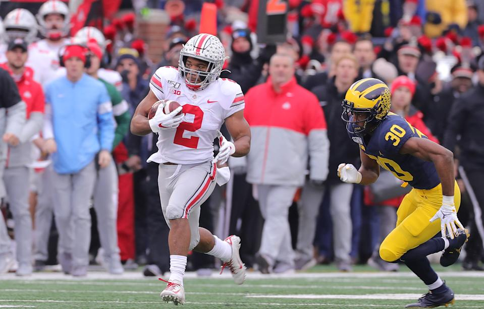 ANN ARBOR, MI - NOVEMBER 30: J.K. Dobbins #2 of the Ohio State Buckeyes runs for a first down during as Daxton Hill #30 of the Michigan Wolverines gives chase during the first quarter of the game at Michigan Stadium on November 30, 2019 in Ann Arbor, Michigan. (Photo by Leon Halip/Getty Images)