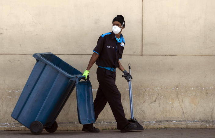 A worker wearing face masks and gloves to protect herself against coronavirus, pulls a rubbish bin whilst cleaning at Chris Hani shopping mall in Vosloorus, east of Johannesburg, South Africa, Friday, March 27, 2020. South Africa went into a nationwide lockdown for 21 days in an effort to mitigate the spread to the coronavirus. The new coronavirus causes mild or moderate symptoms for most people, but for some, especially older adults and people with existing health problems, it can cause more severe illness or death. (AP Photo/Themba Hadebe)