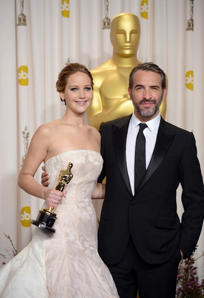 "HOLLYWOOD, CA - FEBRUARY 24:  Actress Jennifer Lawrence, winner of the Best Actress award for ""Silver Linings Playbook,"" and presenter Jean Dujardin pose in the press room during the Oscars held at Loews Hollywood Hotel on February 24, 2013 in Hollywood, California.  (Photo by Jason Merritt/Getty Images)"