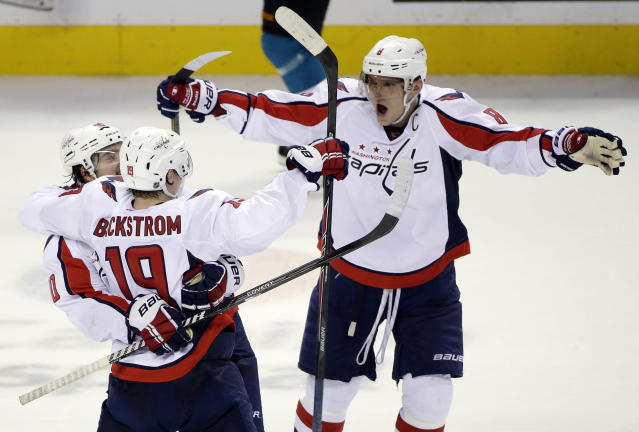 Washington Capitals center Nicklas Backstrom, of Sweden, (19) celebrates his game-winning goal with teammates Marcus Johansson, left, of Sweden, and Alex Ovechkin, of Russia during a shootout in an NHL hockey game against the San Jose Sharks on Saturday, March 22, 2014, in San Jose, Calif. Washington won 3-2. (AP Photo/Marcio Jose Sanchez)