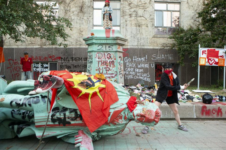 A protester hits the head of Egerton Ryerson's statue