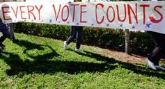 A white sign with red text that says 'Every Vote Counts.'