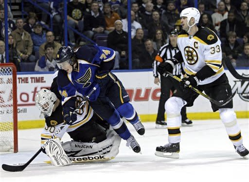 Boston Bruins' Zdeno Chara (33) shoves St. Louis Blues' T.J. Oshie (74) over goalie Tim Thomas (30) in the second period of an NHL hockey game, Wednesday, Feb. 22, 2012 in St. Louis.(AP Photo/Tom Gannam)