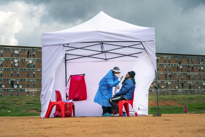 A person gets tested for COVID-19 in a tent