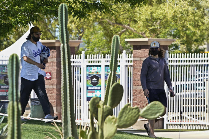 Fans walk past cactuses at Surprise Stadium before a spring training baseball game between the Colorado Rockies and the Kansas City Royals, Sunday, March 21, 2021, in Surprise, Ariz. (AP Photo/Sue Ogrocki)