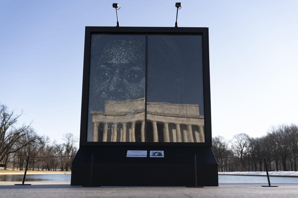 "The installation ""Vice President Kamala Harris Glass Ceiling Breaker"" is seen at the Lincoln Memorial, reflected, in Washington, Wednesday, Feb. 4, 2021. Vice President Kamala Harris' barrier-breaking career has been memorialized in a portrait depicting her face emerging from the cracks in a massive sheet of glass. Using a photo of Harris that taken by photographer Celeste Sloman, artist Simon Berger lightly hammered on the slab of laminated glass to create the portrait of Harris. (AP Photo/Carolyn Kaster)"