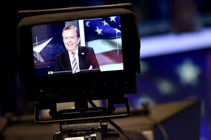 """A monitor on a television camera shows Lou Dobbs hosting """"Lou Dobbs Tonight"""" in 2018."""