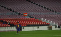 Barcelona's Lionel Messi walks back to his position during the Spanish La Liga soccer match between Barcelona and Valencia at the Camp Nou stadium in Barcelona, Spain, Saturday, Dec. 19, 2020. (AP Photo/Joan Monfort)