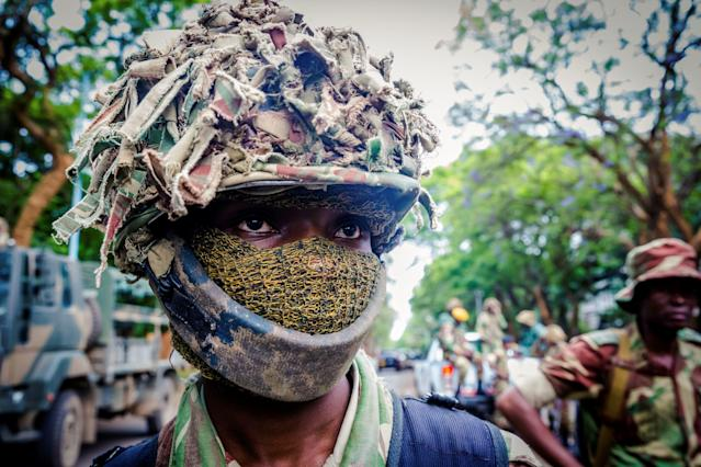 <p>A masked Zimbabwean soldier looks on as people demonstrate to demand the resignation of Zimbabwe's president, near the State House, on November 18, 2017 in Harare. Tens of thousands of overjoyed protesters flooded Zimbabwe's streets on November 18 celebrating the crumbling of president's ruthless regime, which had controlled the country for nearly 40 years. / AFP PHOTO / Jekesai NJIKIZANA (Photo credit should read JEKESAI NJIKIZANA/AFP/Getty Images) </p>