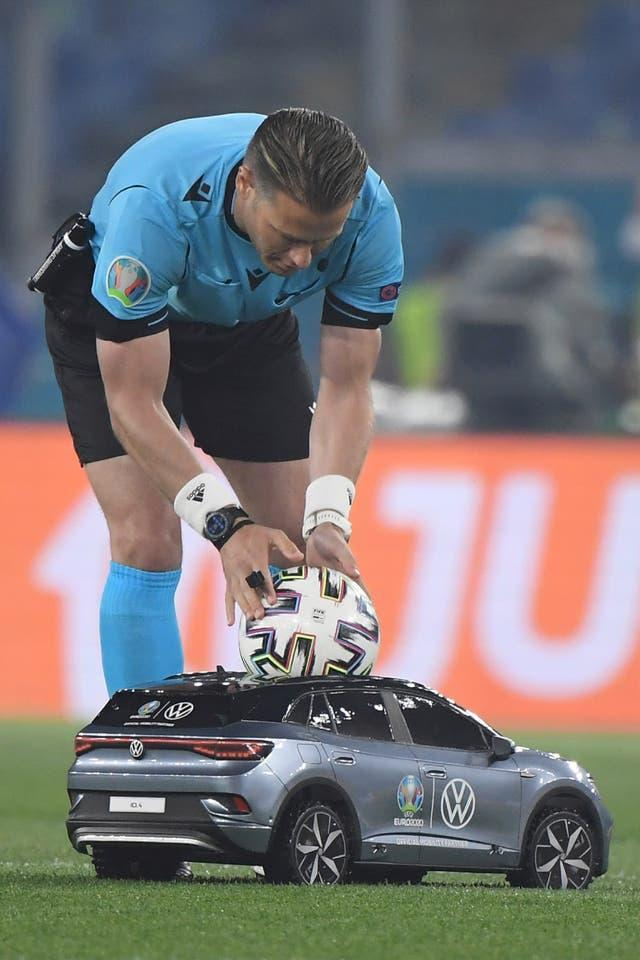 Dutch referee Danny Makkelie picks up the match ball, which was delivered by a remote-controlled car