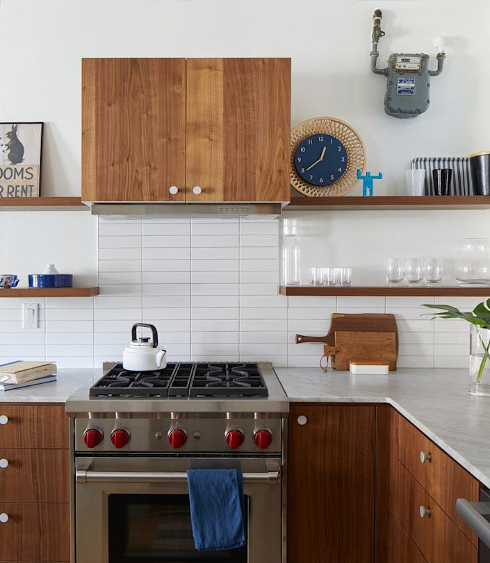 """<div class=""""caption""""> After: The previous version of the kitchen, with white cabinetry and wood countertops, was quite the opposite of the open and airy space the family has now. The update, with its tiled backsplash, <a href=""""https://fave.co/2TiXnLy"""" rel=""""nofollow noopener"""" target=""""_blank"""" data-ylk=""""slk:new range"""" class=""""link rapid-noclick-resp"""">new range</a>, and Carrara marble counter, feels modern and built to last. </div>"""