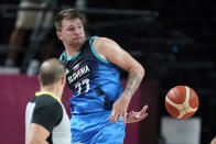 Slovenia's Luka Doncic saves the ball from going out of bounds during a men's basketball preliminary round game against Spain at the 2020 Summer Olympics, Sunday, Aug. 1, 2021, in Saitama, Japan. (AP Photo/Charlie Neibergall)