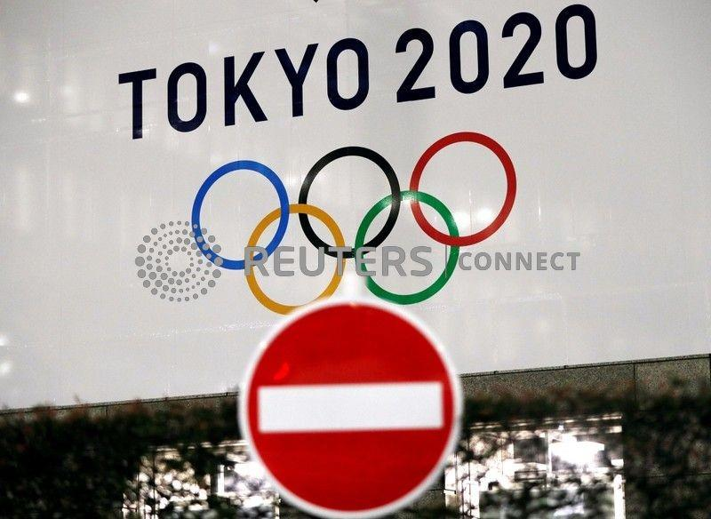 A banner for the upcoming Tokyo 2020 Olympics is seen behind a traffic sign in Tokyo, Japan