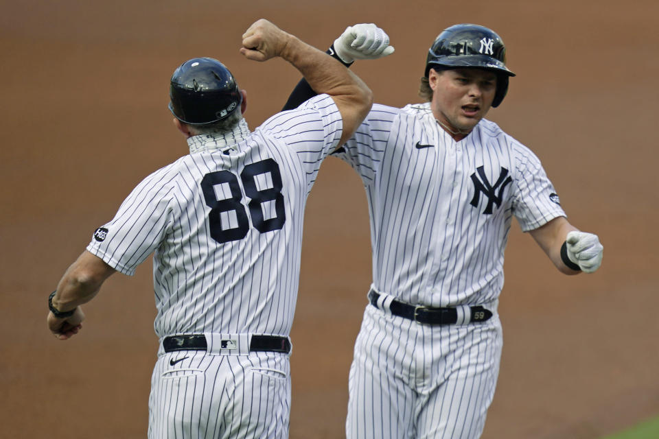 New York Yankees first baseman Luke Voit, right, celebrates with third base coach Phil Nevin (88) after Voit hit a solo home run against the Tampa Bay Rays during the second inning in Game 4 of a baseball American League Division Series Thursday, Oct. 8, 2020, in San Diego. (AP Photo/Gregory Bull)