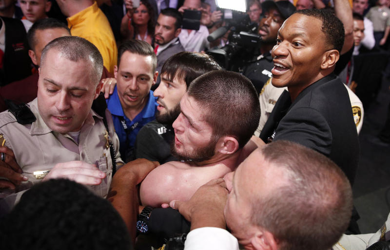 Khabib Nurmagomedov, bottom center, is held back outside of the cage after fighting Conor McGregor in a lightweight title mixed martial arts bout at UFC 229 in Las Vegas, Saturday, Oct. 6, 2018. Nurmagomedov won the fight by submission during the fourth round to retain the title. (AP Photo/John Locher)