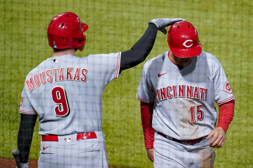 Cincinnati Reds' Nick Senzel, right is greeted by Mike Moustakas after he scored on a double by Jesse Winker during the eighth inning of a baseball game against the Pittsburgh Pirates, Tuesday, May 11, 2021, in Pittsburgh. (AP Photo/Keith Srakocic)